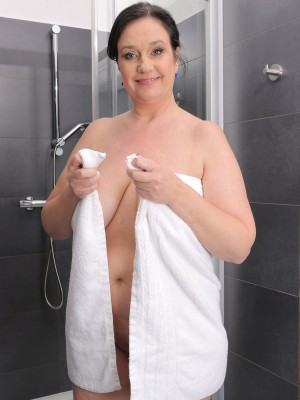 Large and big-boobed Ria Darksome from AllOver30 getting herself wet in the following