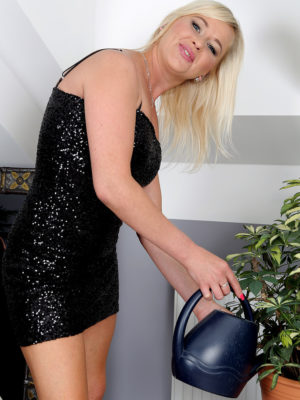 Beatiful blond Evelina Jones waters her plants and taunts
