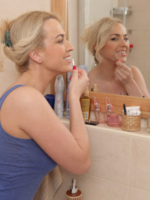 Blonde Eve Valentine admires herself in mirror
