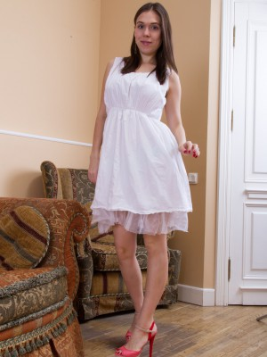 Agneta disrobes about sofa from white dress sexily