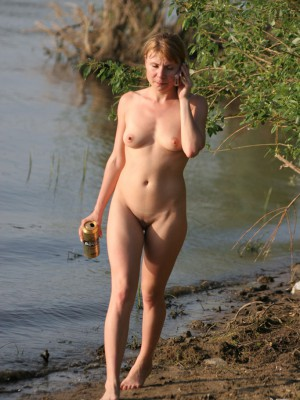 Cute nude girl having a cold drink whilst strolling inside the water
