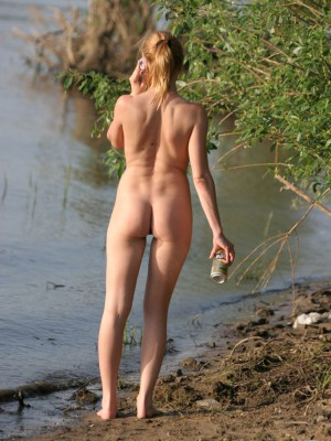 Nude redhead girl strolling found on the beach speaking about her mobile phone