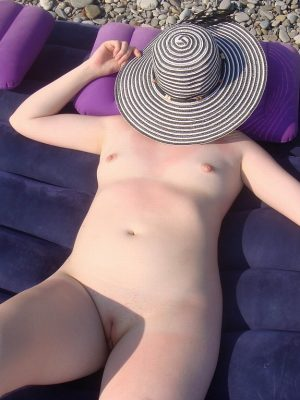 Blue-eyed beauty nude on the shore gets a sunburn
