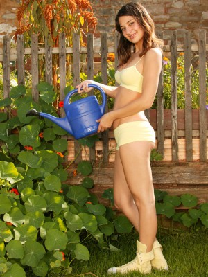 Cute bare chick likes tugging in the big garden