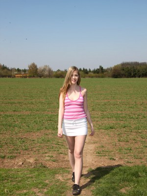 A daring and fairly naked teenager drains on some grass